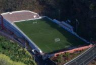 Campo de fútbol sobre edificio de oficinas y entre montañas